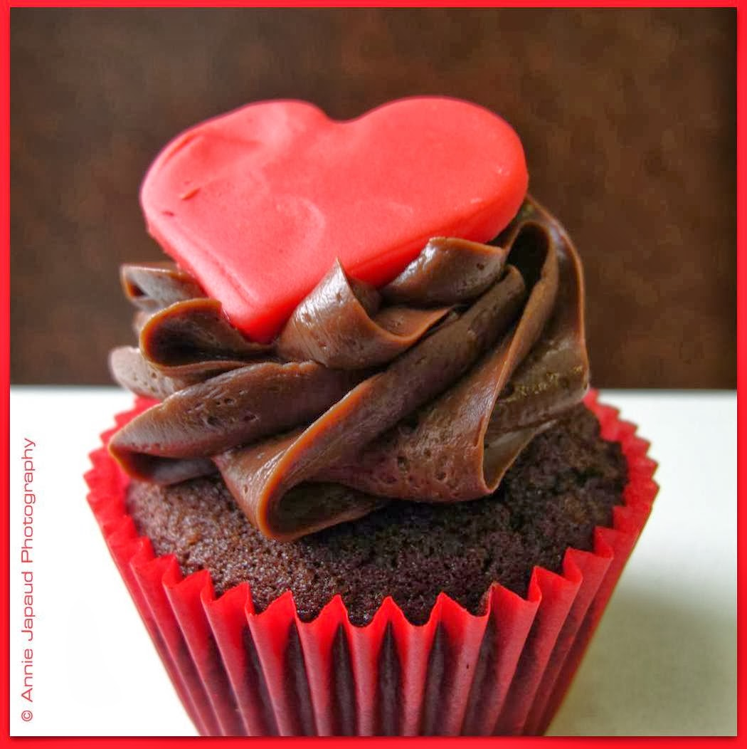 image of a cup-cake with big read heart on top of chocolate cream filling  with red coloured casing