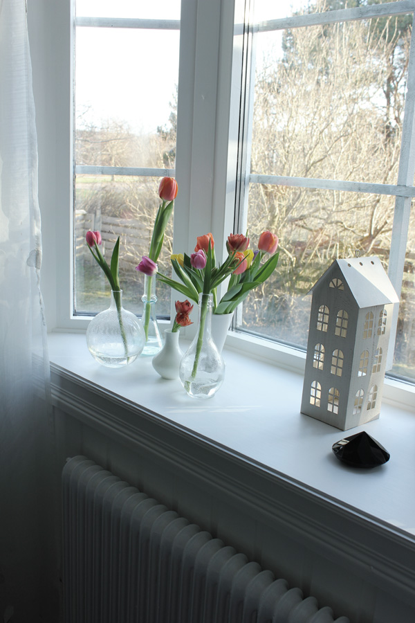 tulpaner i små glasflaskor i fönstret, burspråk, prydnad diamant, plåthus dekoration