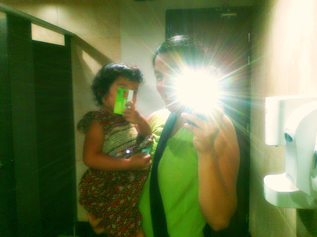 Mama & Kecil taking self photo in the restroom mirror