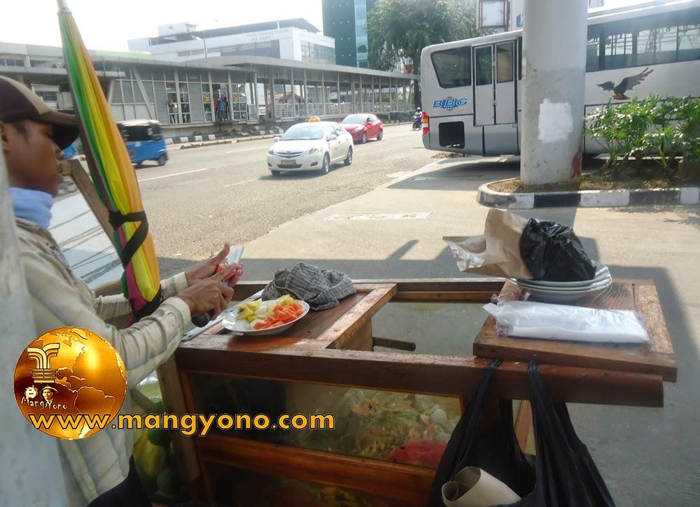 FOTO : Mang Rujak, sedang meracik rujak pesanan admin di depan SPBU Jelambar.