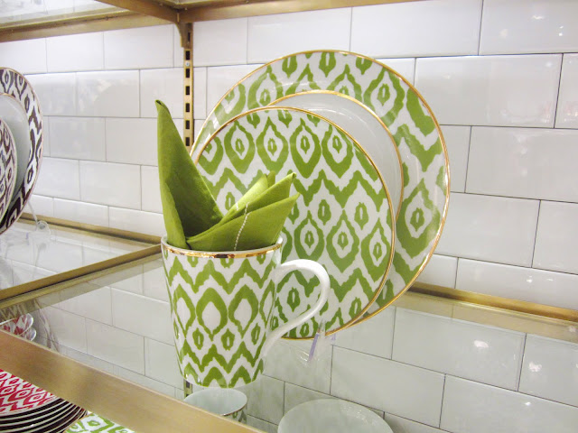 Green and white ethnic print ceramic dish ware on a floating, glass shelf with subway tile walls