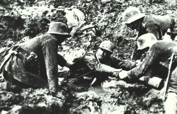 German troops trying to rescue what looks like a French soldier from sinking in a mud hole. Northern France, 1914-1918