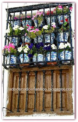 Foto de janela com vasos de flores numa rua em Granada, Espanha