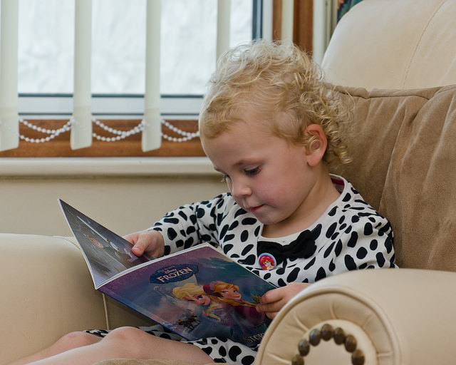 girl sitting on armchair reading frozen book