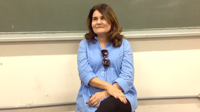 Professora Joana Belarmino, sentada em frente à uma lousa, dentro de uma sala de aula da universidade federal do Paraná, vestida com uma camisa azul clara, durante a entrevista concedida ao professor Marco Bonito, sobre comunicação, cidadania e acessibilidade para as pessoas com deficiência visual.