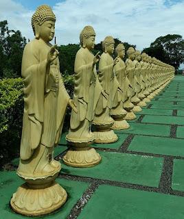 Estátuas amarelas de mulheres dão boas-vindas ao visitante.