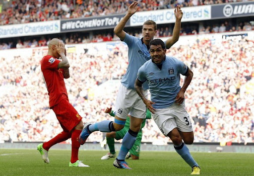 Martin Škrtel holds his head in his hands as Carlos Tévez celebrates after scoring