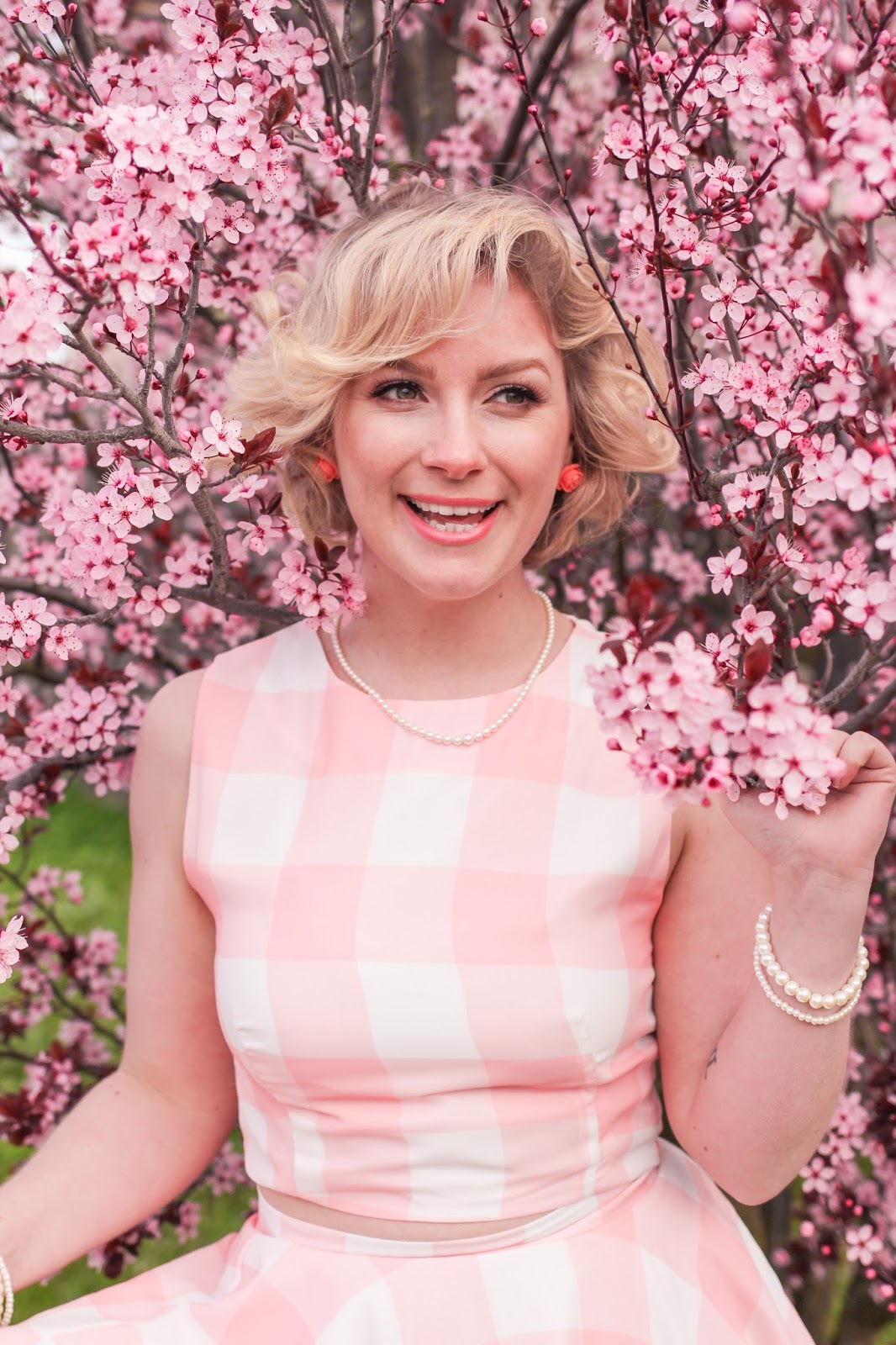 @findingfemme in pink gingham Chicwish crop top and skirt set, enjoying spring cherry blossoms.