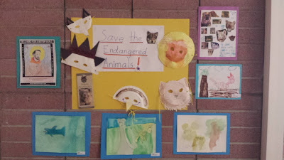 Animal masks cut out of paper plates arranged on yellow posterboard surrounding a sign that reads, 'Save the Endangered Animals!' Surrounding the posterboard are pieces of student artwork individually arranged on blue posterboard, including a picture of Francis, patron saint of the animals,  watercolor images and a collage cutout of magazine images of cats arranged on purple posterboard.