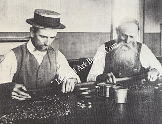 Two diamond sorters at work in Kimberley at the turn of the century. The sieves help them to sort the rough diamonds into size groups.