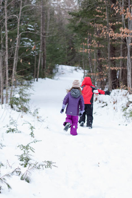 two children running through snowy woods