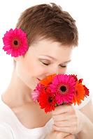 mujer aspirando el perfume de unas flores