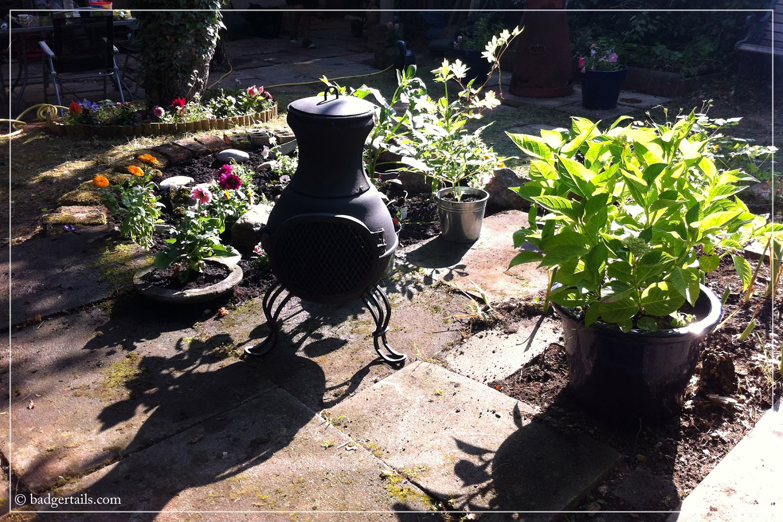 english garden in summer with chiminea