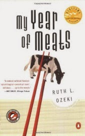 Cover art for My Year of Meats, featuring a small plastic toy of a black and white cow. The cow is posed with its head down, as though it's grazing, and is held upright between two red chopsticks against a white background.