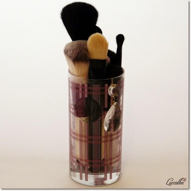 Brochas de maquillaje en un vaso de vela