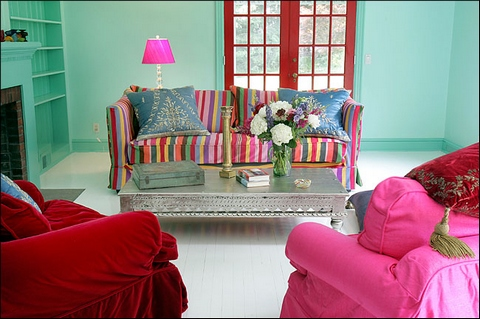 [A colorful interior with a striped couch and two armchairs]