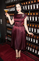 Dita Von Teese posing on the red carpet with a drink in her hand