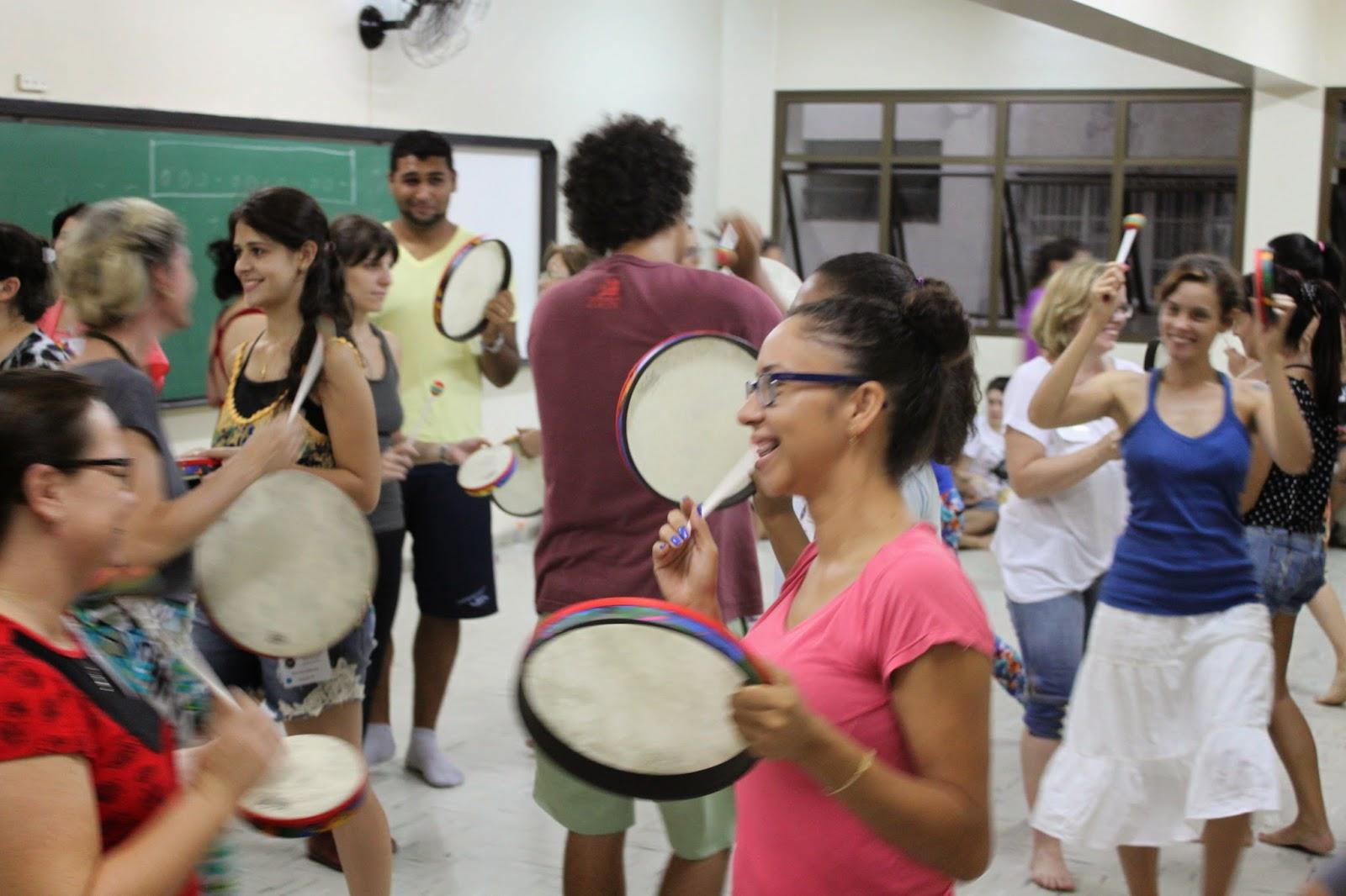 Descrição da Foto: Participantes estão caminhando em diversas direções tocando o tambor. Todos sorridentes.