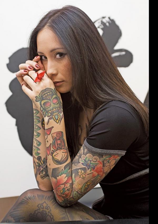 preciosa mujer japonesa nos mira de reojomientras vemos tatuajes en sus brazos de vivos colores
