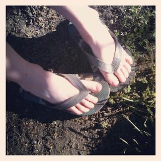 Pés de menino usando chinelos de dedo