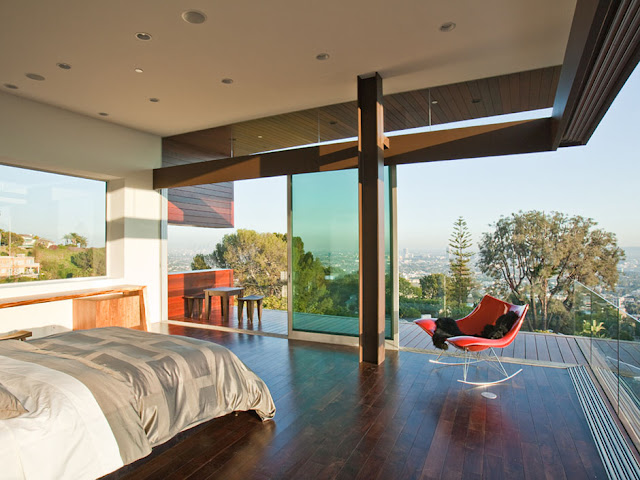 Picture of the large bed in the bedroom with red swaying chair and beautiful city views