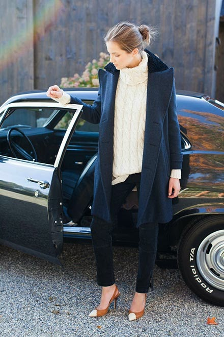 Model wearing a long navy peacoat and a chunky sweater