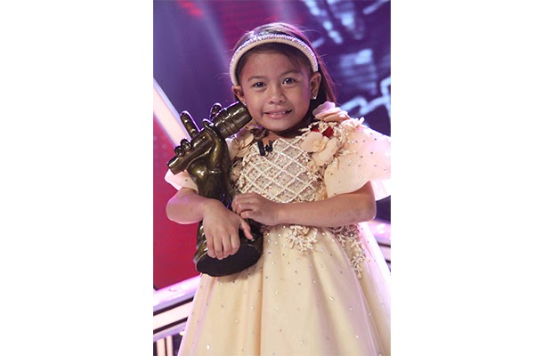 Lyca holding her The Voice Kids Grand Champion trophy