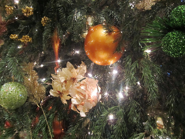 close up of a Christmas tree with green and gold ornaments