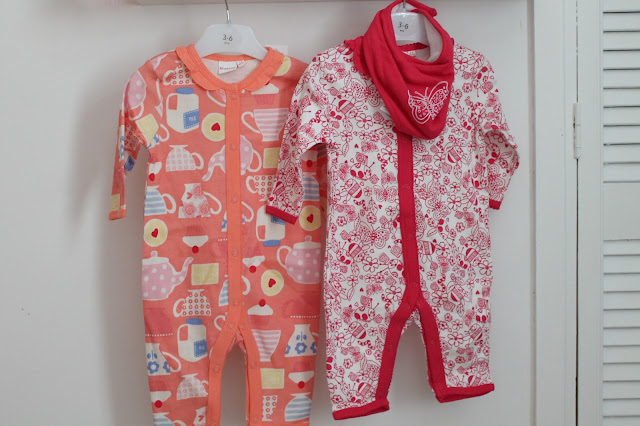 Orange sleepsuit with cupcake, teacup and teapot pattern, white sleepsuit with red doodles all over and a red bib