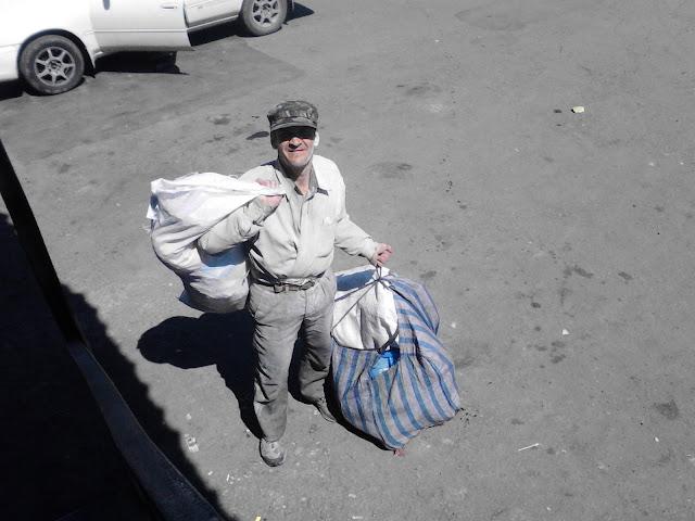 Бомж стоит с большими сумками