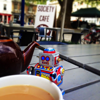 A toy robot enjoying a cup of tea at Society Cafe, Bath