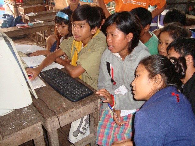 Students crowd around a single computer