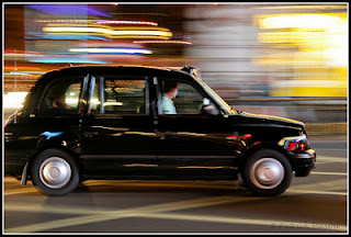 Black London cab in the street at night