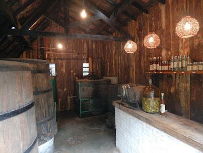 No mesmo local um pequeno alambique comercializa cachaças artesanais. O cheiro de madeira se mistura ao odor da pinga e aguça o paladar.