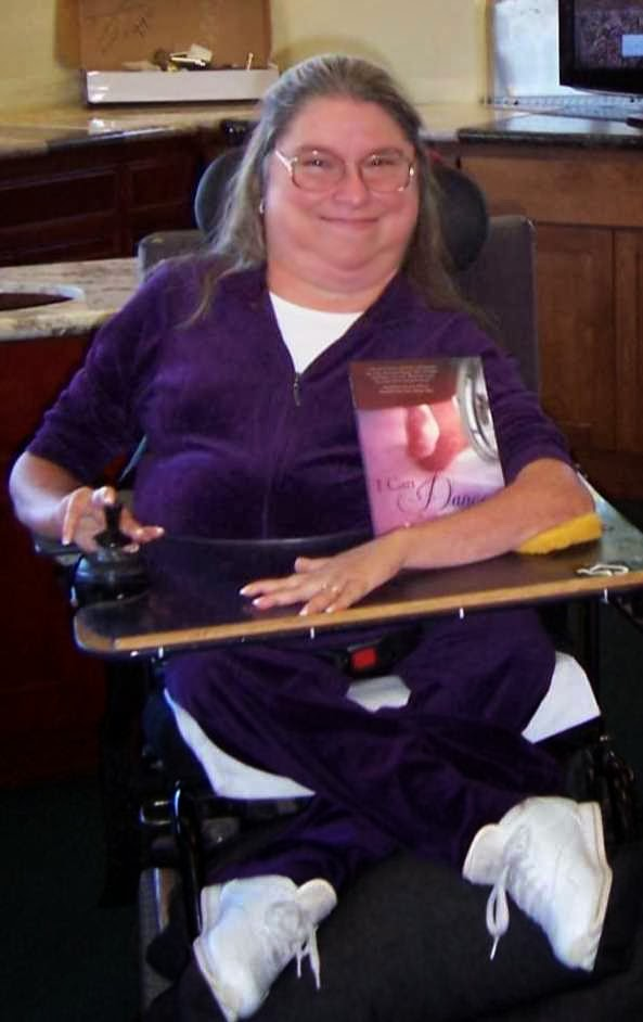 "picture of luarie with her book ""i can dance"" Laurie is smiling and wearing a purple jumpsuit and uses a power wheelchair"
