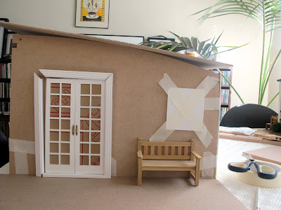 Side view of a taped-together modern dolls' house miniature kit, with a set of white french doors propped against the wall and a park bench next to them.