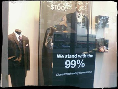 Closed Mens' Warehouse with 'We Support the 99%' sign in window