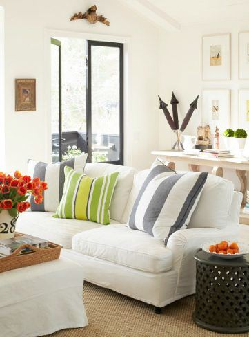 close up of white sofas with striped accent pillows and black trimmed windows