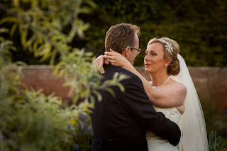 A couple embrace after getting married, bride has a beautiful jewelled hair accessory and veil and a classic low bun hairstyle