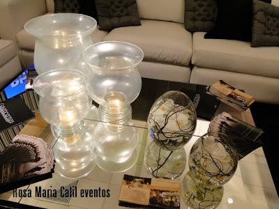 mesa centro espelhada, trio de velas em taças peroladas, almofadas pretas, almofadas prata, orquídeas brancas
