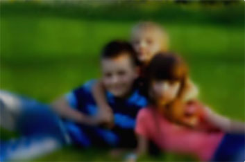 Blurry image of three kids posing for a photo laying on grass.