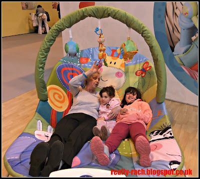 Nanny and girls relaxing in giant baby bouncer