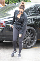 Kim Kardashian black leggings and revealing black top