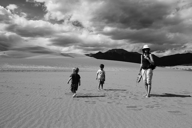 A family of hikers in the sand at Great Sand Dunes.