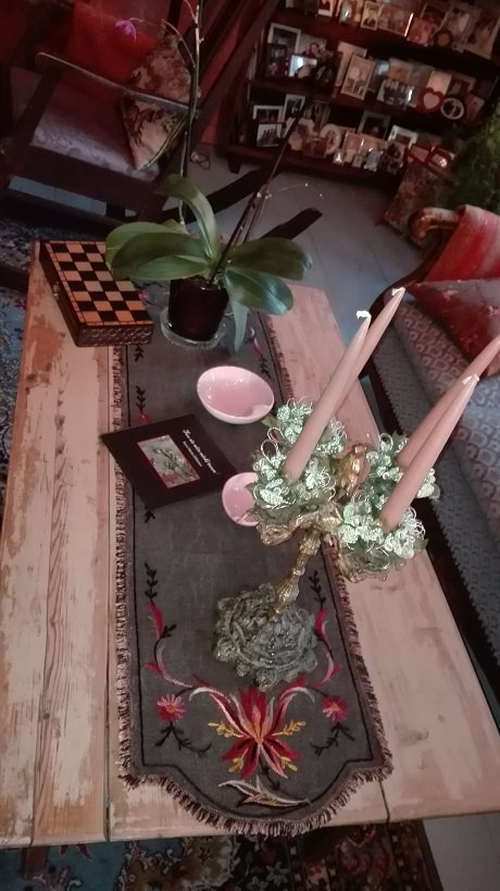 Olohuoneen pöydällä on tumma, taidokkaasti suunniteltu ja merkattu pöytäliina.