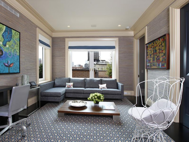Home office or study in an apartment with black floor, blue and white graphic print area rug, blue grey sectional sofa, white wire arm chair, a low coffee table, windows with roll up shades and a black desk with a grey rolling chair