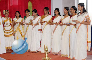 Kerala girls wearing traditional white saree with loose hair style at eve of Onam celebrations.