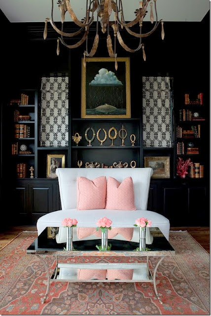 living area with black walls and pink pillows