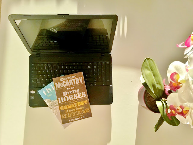 Laptop with two books and orchid plant