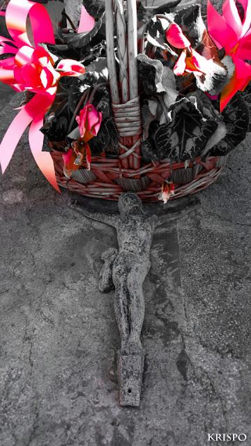 centro de flores y crucufijo de piedra en tumba